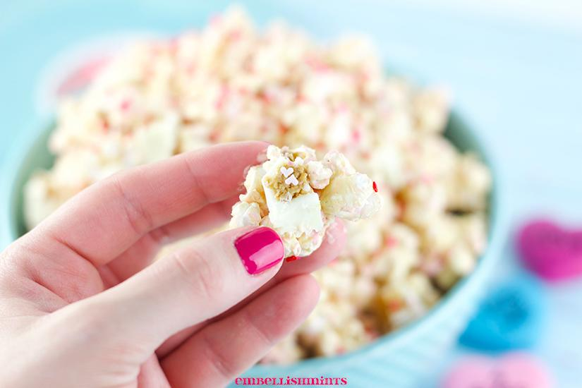 This White Chocolate Peanut Butter Popcorn is a perfect Valentine's Day treat! A blend of white chocolate, peanut butter, peanuts, and Reese's White Chocolate Peanut Butter Cups! Find the recipes on www.Embellishmints.com