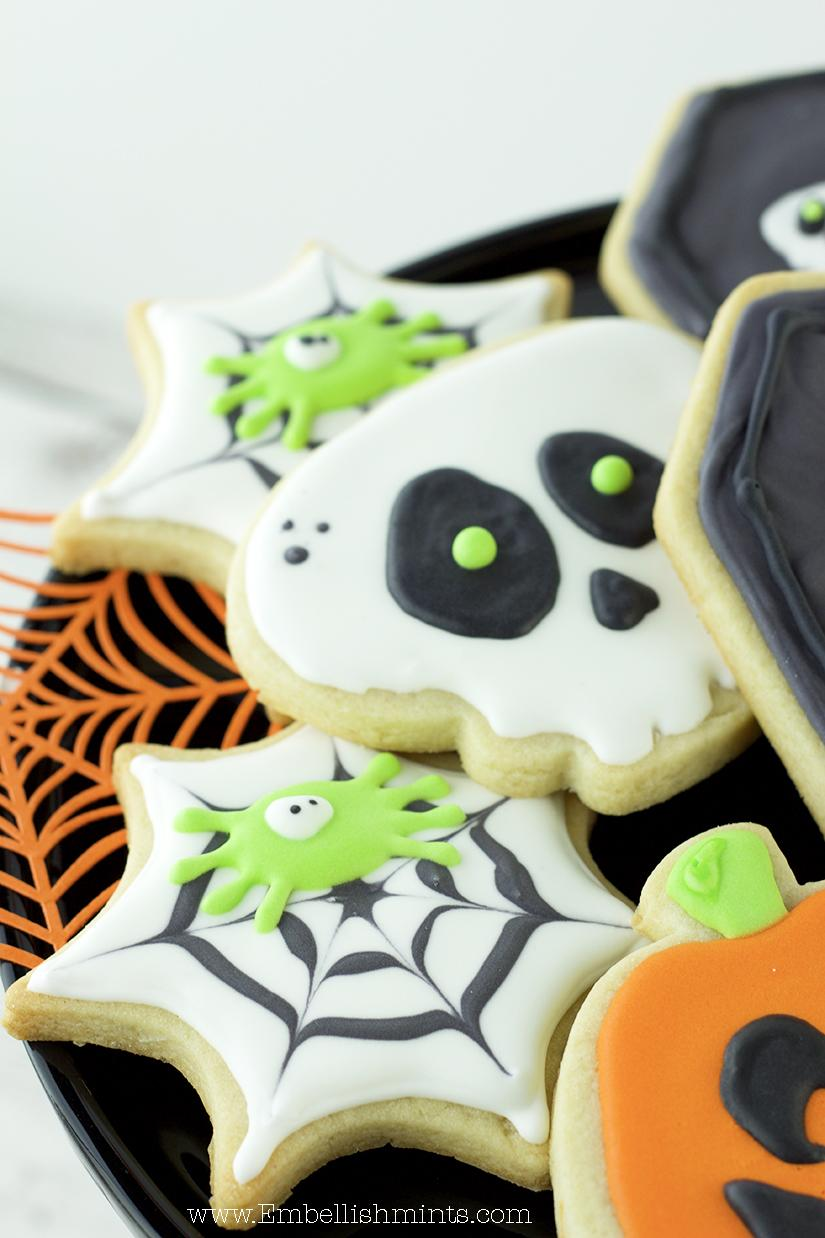 Watch how I made these super fun Halloween Spiderweb Cookies using Royal Icing. Get inspired for Halloween with these Spiderweb Cookies. www.Embellishmints.com
