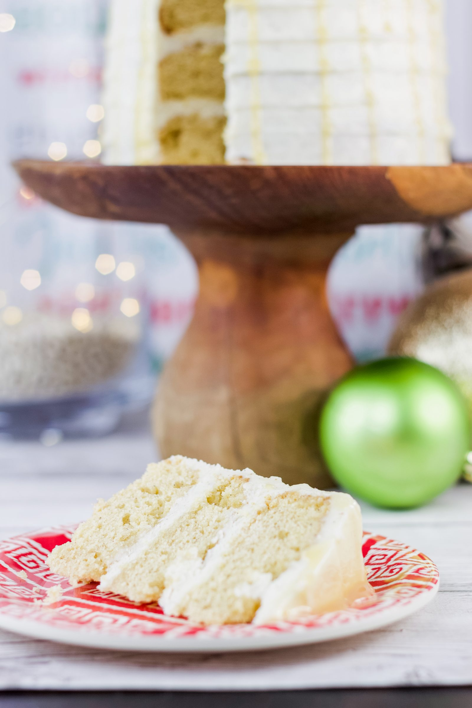 This eggnog cake recipe is everything you need to get into the holiday spirit! Topped with a rum simple syrup and cream cheese frosting, it's a must try! Find the recipe on www.Embellishmints.com